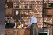 Fotografia vista laterale della donna che prepara alla cucina