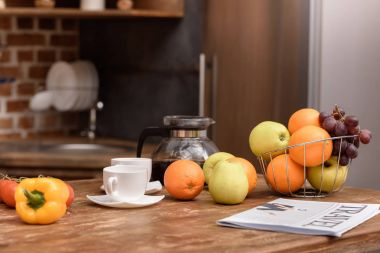cups with coffee and vegetables with fruits on wooden table in kitchen