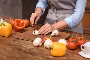 cropped image of woman cutting mushrooms on wooden board in kitchen