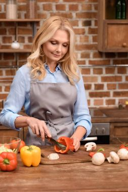 woman cutting red bell pepper on wooden board