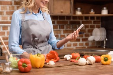 cropped image of woman looking at smartphone in kitchen