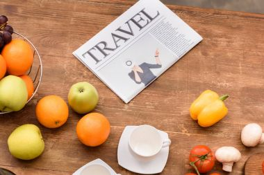 high angle view of travel newspaper and fruits with vegetables on wooden table