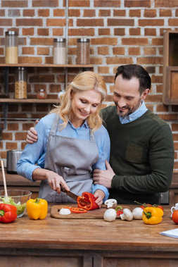 husband hugging wife while she cutting vegetables in kitchen