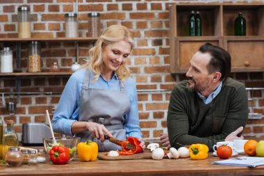 smiling husband looking at wife while she cutting vegetables