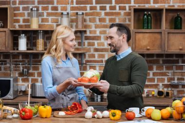 husband giving plate with vegetables to wife