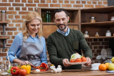 wife cutting vegetables and husband putting plate on table