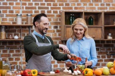 happy couple preparing salad in kitchen
