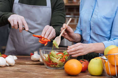 Cropped image of couple preparing salad stock vector