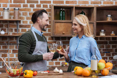 happy husband and wife clinking with glasses of wine in kitchen