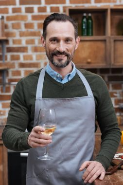 smiling man holding glass of wine and looking at camera in kitchen