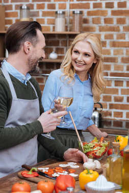 smiling husband and wife clinking with glasses of wine