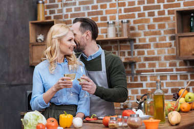 husband and wife clinking with glasses of wine in kitchen