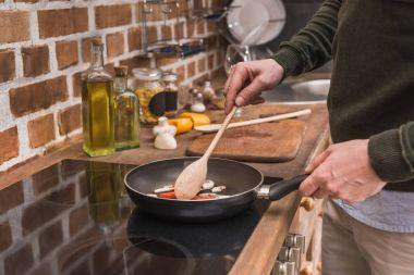 cropped image of man stirring vegetables on frying pan