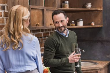 smiling husband with glass of wine talking to wife in kitchen