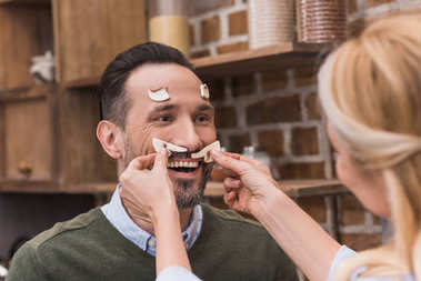 wife putting pieces of mushrooms on husband face