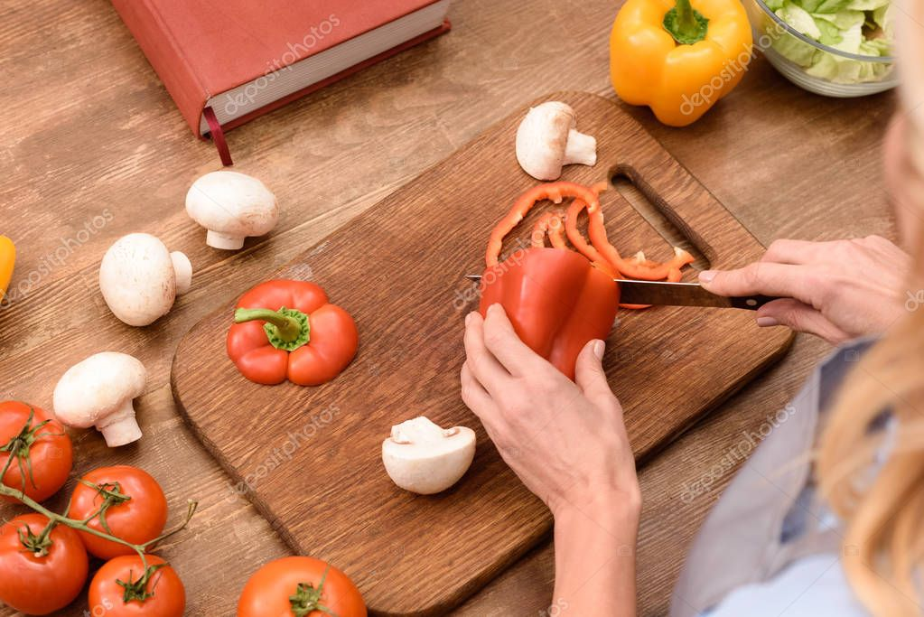 cropped image of woman cutting bell pepper in kitchen