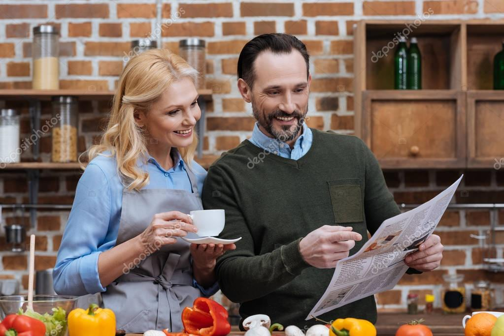 wife drinking coffee and husband reading newspaper