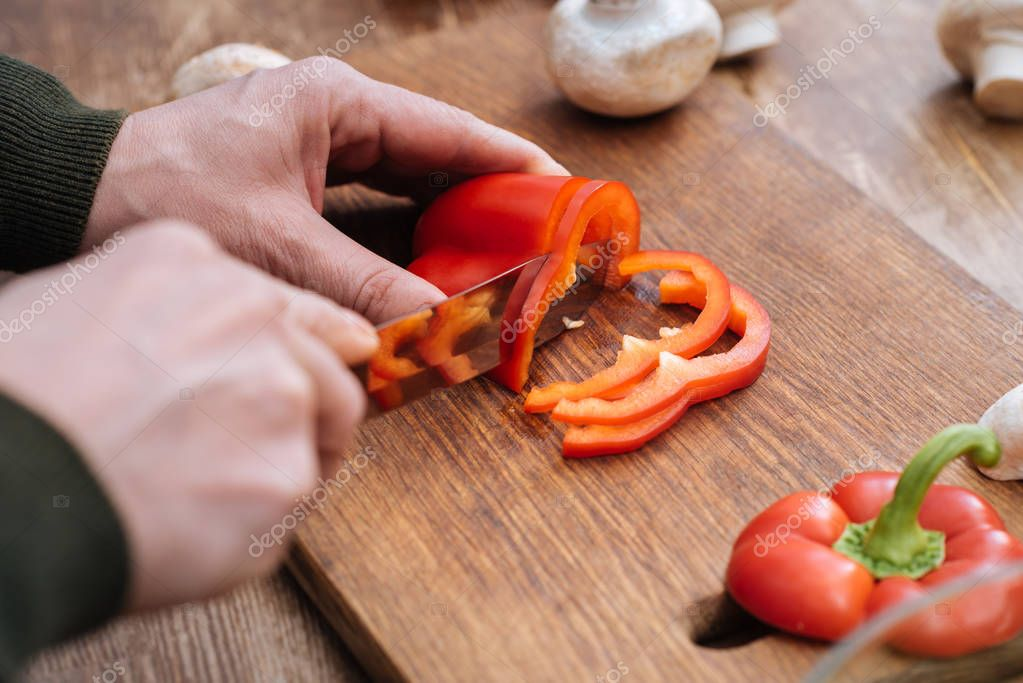 cropped image of man cutting bell pepper in kitchen