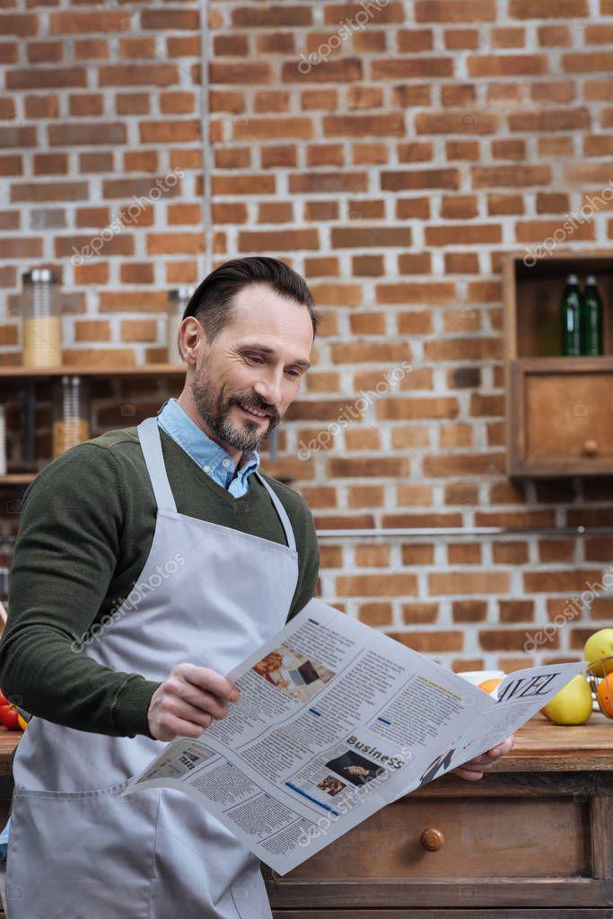 handsome man reading travel newspaper in kitchen