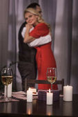Photo couple hugging with candles and wine in glasses on foreground