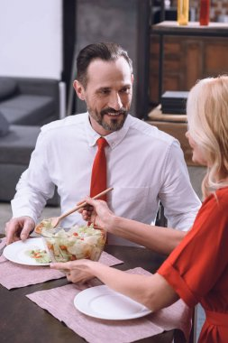 wife putting salad on smiling husband plate at romantic date