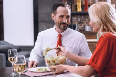 wife putting salad on husband plate during romantic dinner