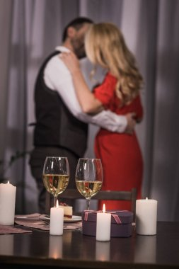 heterosexual couple standing and kissing at home with wineglasses on foreground