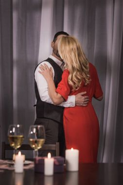heterosexual couple standing and kissing at home at romantic date