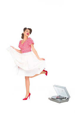 woman in pin up style clothing dancing near phonograph isolated on white