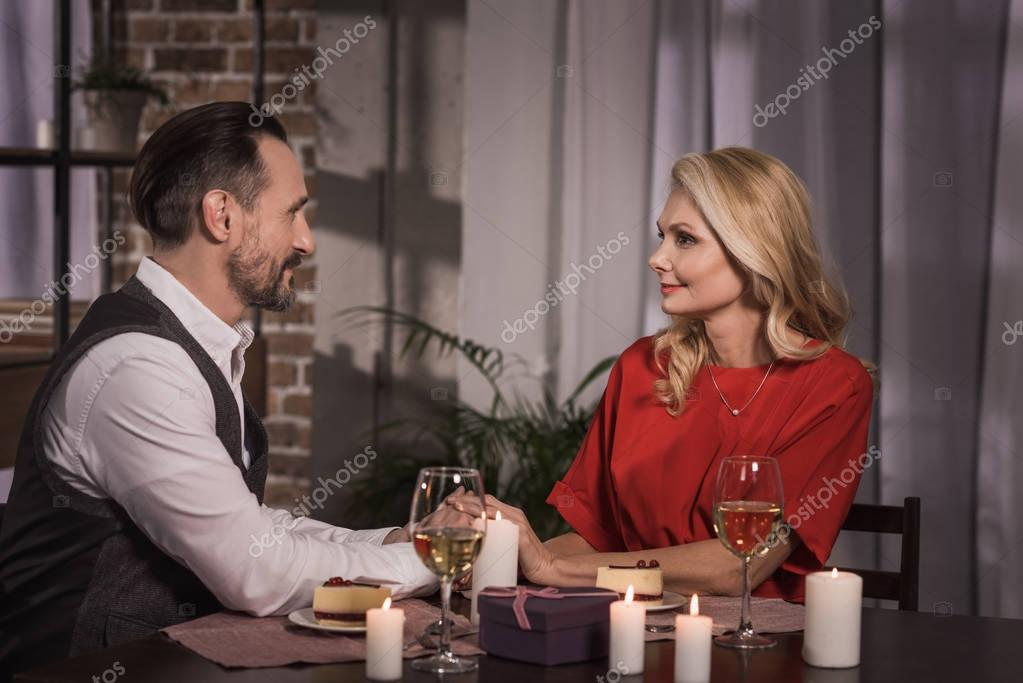 side view of couple holding hands and looking at each other at romantic date