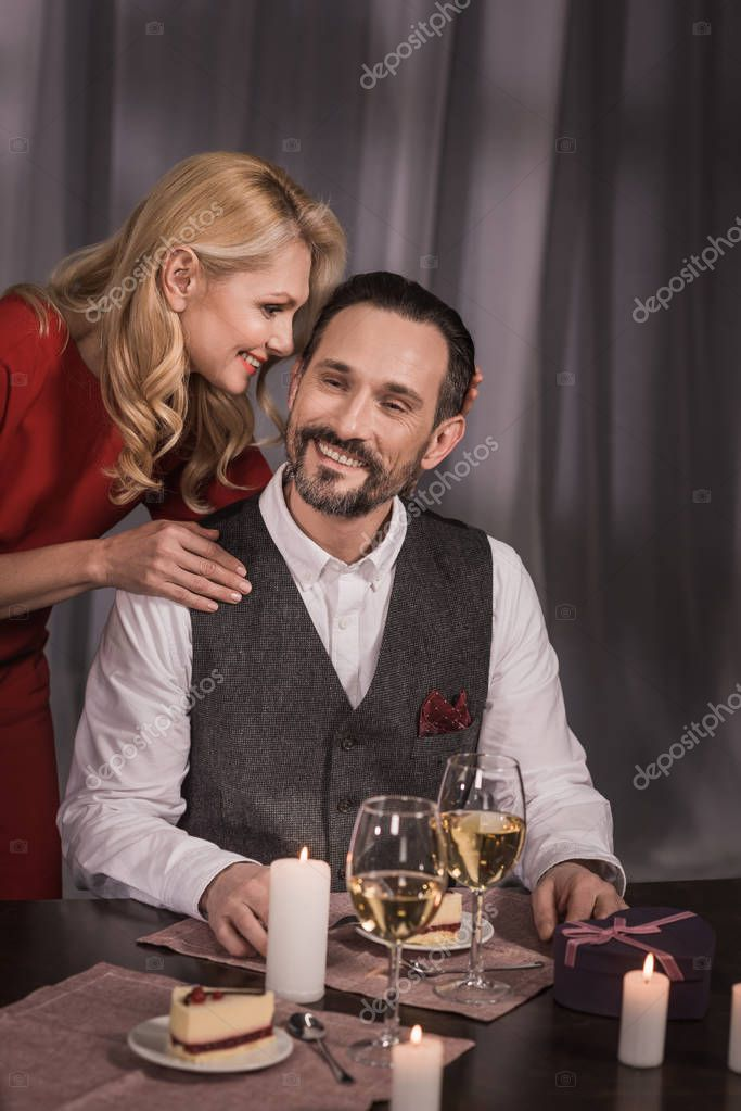 wife hugging husband and saying something during dinner