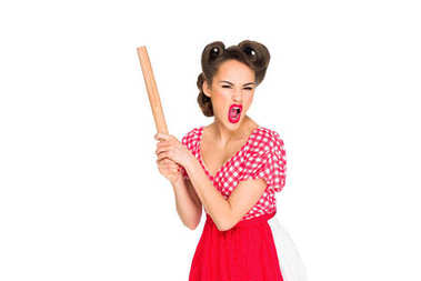 angry stylish woman in retro clothing and apron with rolling pin isolated on white