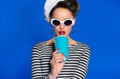 portrait of stylish young woman with beverage in paper cup isolated on blue
