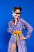 portrét módní ženy v retro stylu oblečení mluví o smartphone, samostatný na modré