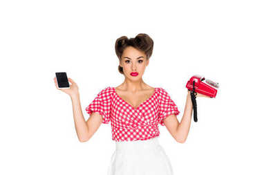 Portrait of stylish woman in retro clothing holding smartphone and old telephone isolated on white stock vector