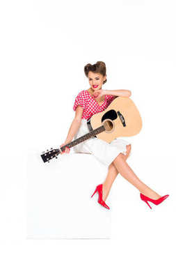 attractive young woman in retro clothing with guitar sitting on cube isolated on white