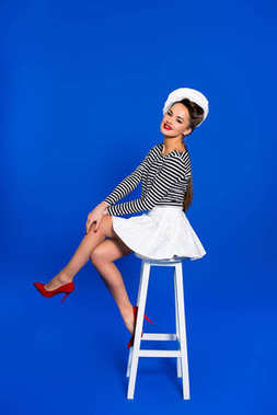 beautiful young woman in sailor shirt sitting on chair isolated on blue