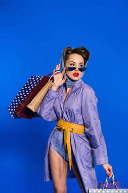 portrait of stylish woman in retro clothing with shopping bags isolated on blue