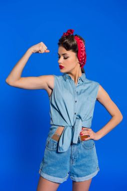 portrait of young woman in retro clothing showing muscles isolated on blue