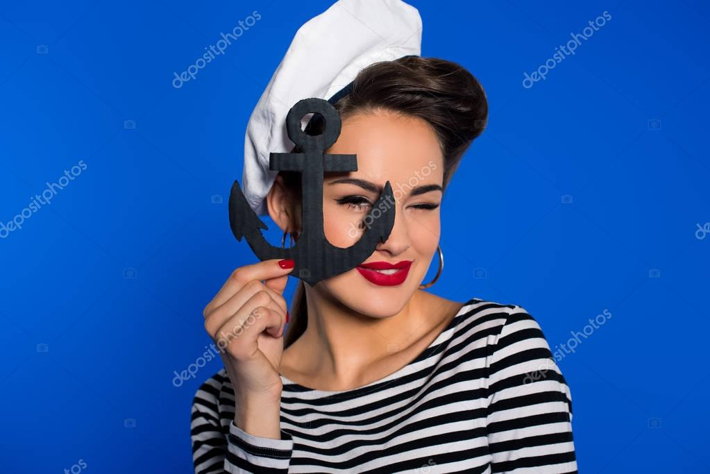 portrait of fashionable young woman in retro clothing with anchor in hand isolated on blue