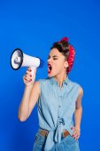 Photo fashionable young woman in pin up style clothing with loudspeaker isolated on blue
