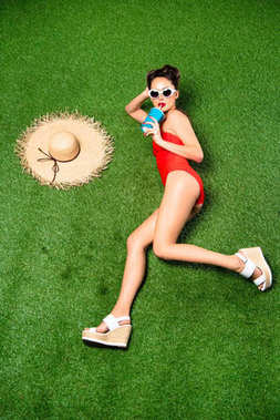 Overhead view of stylish young woman in swimming suit with drink lying on green grass stock vector