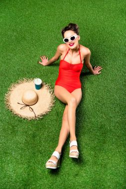 overhead view of stylish young woman in swimming suit with straw hat resting on green grass
