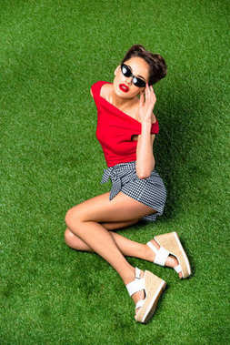 overhead view of beautiful woman in sunglasses resting on green lawn