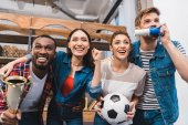 begeistert junge multiethnischen Freunde Fussball zu Hause passen zusammen