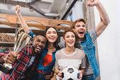 Fotografie begeistert junge multiethnischen Freunde mit Fußball und Trophäe jubeln gemeinsam zu Hause