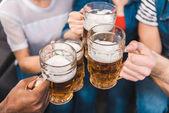 Fotografie částečné zblízka mladí přátelé, v rukou držel sklenice piva