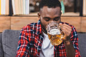 young african american man drinking beer while sitting on sofa at home