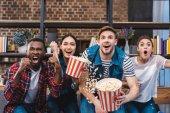 emotionale jungen multiethnischen Freunde Essen Popcorn und vor dem Fernseher
