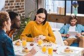 Fotografia ritagliata colpo di amici multietnici guardando ragazza asiatica utilizzando smartphone al tavolo e giovane che per mezzo della compressa digitale dietro